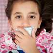 Small girl sick with the flu covering her mouth