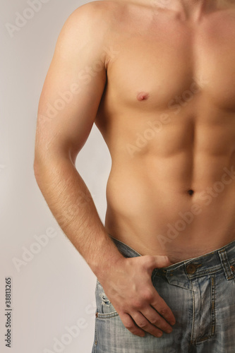 young muscular man , isolated on grey background