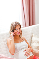 Young pregnant woman sitting on divan and speaking mobile