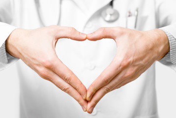 Young doctor with heart shaped hands on white background
