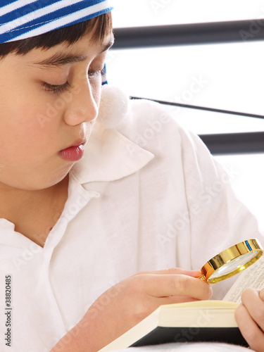 boy reading a book with a magnifying glass