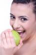 glückliche junge frau beisst in einen grünen apfel