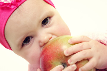 Baby holding and eating an apple, isolated on white