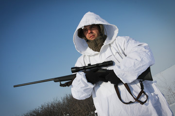 Hunter in white camouflage suit with sniper