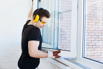 Man worker mounting window