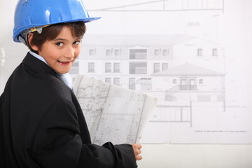 Young boy examining architectural drawings
