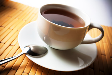 cup of tea in a white cup on a bamboo background
