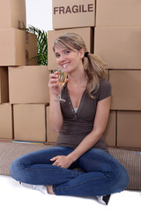 Woman drinking champagne surrounded by packing boxes