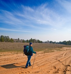 traveler walking by a sandy road