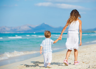 Young girl and boy playing happily at pretty beach