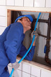 Plumber feeding blue pipe behind a tiled wall
