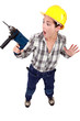 A scared female construction worker with a drill.