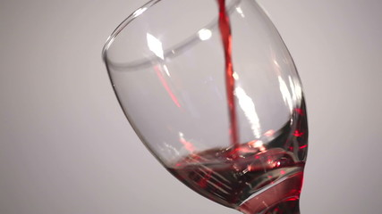Glass glass with bright wine flowing in it