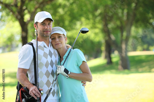 Golfing couple hugging on a course
