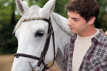 young man with white horse