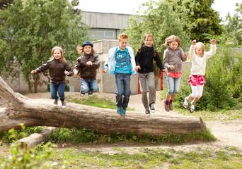 Gruppe Schulkinder springt von Baumstamm