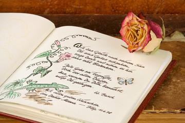 Poesiealbum mit altem Buch und Rose