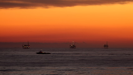 Ocean Sunset - Oil Rig Drilling Platforms on Horizon