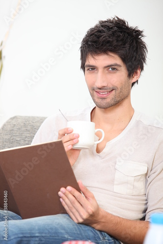 young man reading a book and drinking coffee on a couch