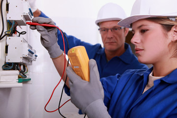 Tradeswoman using a multimeter