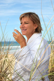 Woman drinking a glass of water on a sand dune