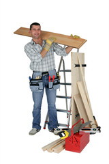 A handyman carrying a wooden plank