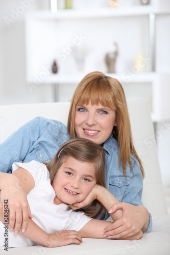 a 35 years old mother and her little girl lying down on a couch
