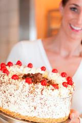 Bäckerin oder Konditorin mit einer Torte