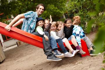 Lehrer und Kinder auf der Rutsche
