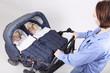 Mutter schiebt Zwillingskinderwagen mit Ihren Töchtern