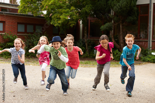 Leinwanddruck Bild Gruppe Kinder läuft auf Schulhof
