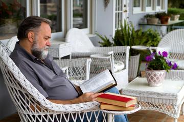 Man Reading Bible On Porch