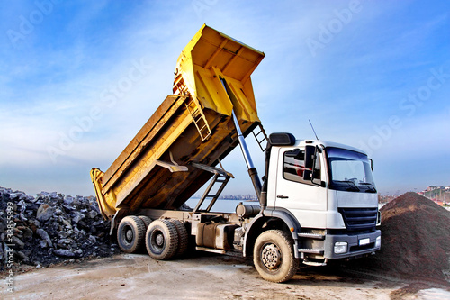 Dump truck is dumping gravel on an excavation site