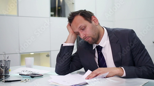 Young businessman overwhelmed by too much paperwork in office