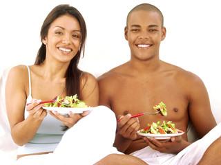 Pareja latina comiendo ensalada de vegetales.