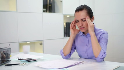 Young businesswoman having headache in the office