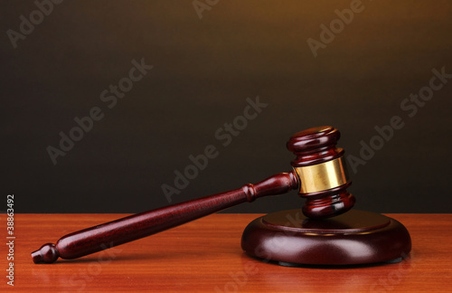 Judge's gavel on wooden table on brown background