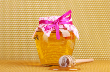 Jar of honey and wooden drizzler on yellow honeycomb background.