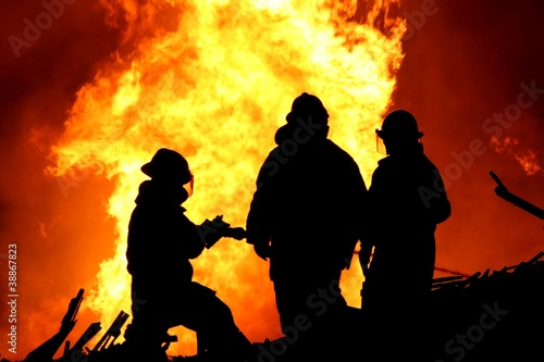 Three fire fighters and huge flames