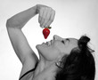 Sexy mature woman eating a strawberry
