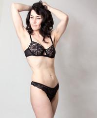 Beautiful mature woman in lingerie posing in studio