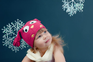 Girl in winter hat framed by snowflakes