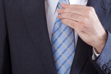Hombre de negocios anudándose su corbata