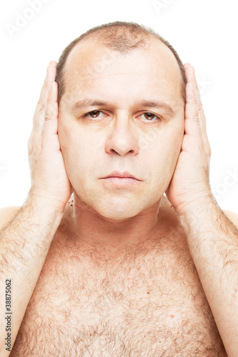 Naked man covering his ears