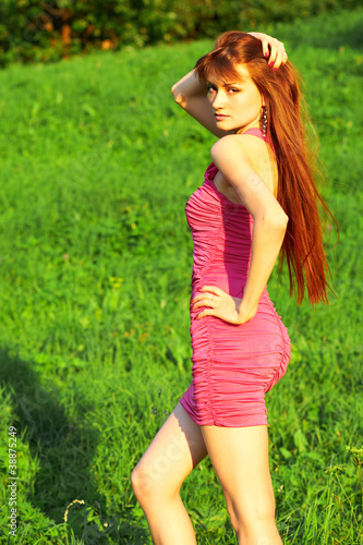 Young beautiful redhead woman on grass