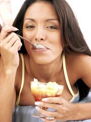 Mujer hispana comiendo helado de frutas.