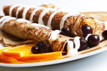 Rolled pancakes with berries and sour cream
