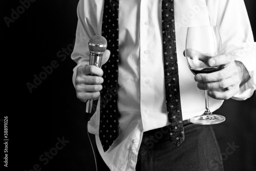 Man with untucked shirt holding a drink and a microphone