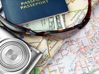 Travel necessities: sunglasses, passports camera on the map
