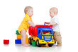 two little children playing with color toys and truck